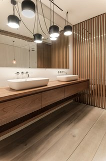 In the master bathroom, the teak vanity and wood screens were designed by Isaac-Rae and custom built by a furniture maker. The sinks by Apaiser were also made custom. The lighting is by Flos.