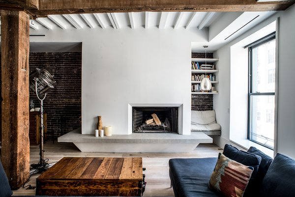 "In the living room, the team raised the firebox, cladded the hearth in a tactile plaster finish, and installed a floating limestone bench that wraps the column. On the left (unseen) is integrated firewood storage, and a cozy reading nook sits on the right. ""The bench was designed to be used as a social space/lounge, and is well-used,"" says Coffey. The wood beams and red brick were scraped and stripped many times to remove the silver paint and reclaim a natural state."