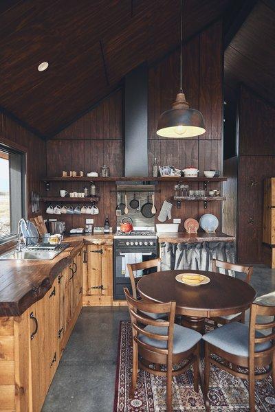 """The rustic cabinetry was built by a family friend and is topped with pine slabs. """"We kept all the imperfections, chainsaw markings and undulations in the live edge,"""" says Kenny."""