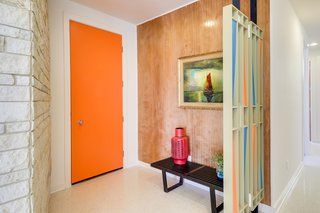 In the entry, an orange door and period-appropriate privacy screen set the tone.