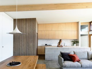 In the open plan kitchen, dining room, and living room, the materials palette was kept very simple and restrained, with a burnished concrete floor, kitchen island composed of unfinished concrete block, and plywood cabinets. A pantry sheathed in vertical planks of contrasting wood anchors the open space.