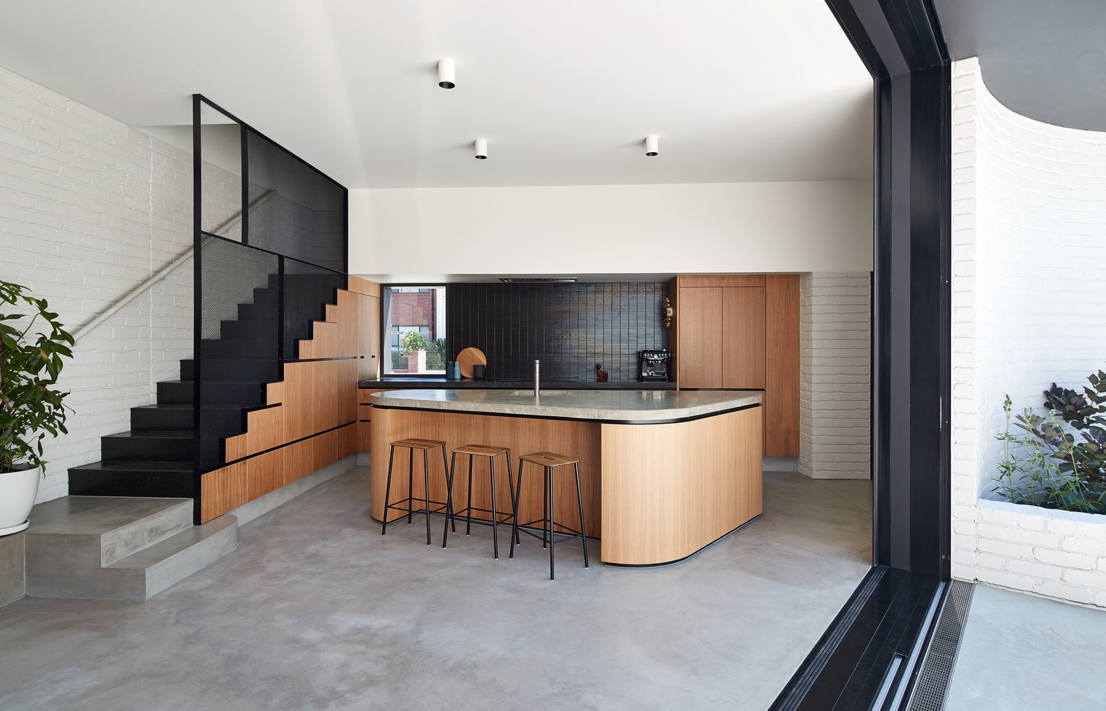 Kitchen, Undermount Sink, Concrete Counter, Ceiling Lighting, Concrete Backsplashe, Concrete Floor, Refrigerator, and Wood Cabinet In the new kitchen, oak timber veneer joinery unites concrete floors and counters.  Photos from An Australian Home's Brick Addition Creates a Private Backyard Haven