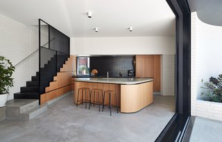 In the new kitchen, oak timber veneer joinery unites concrete floors and counters.