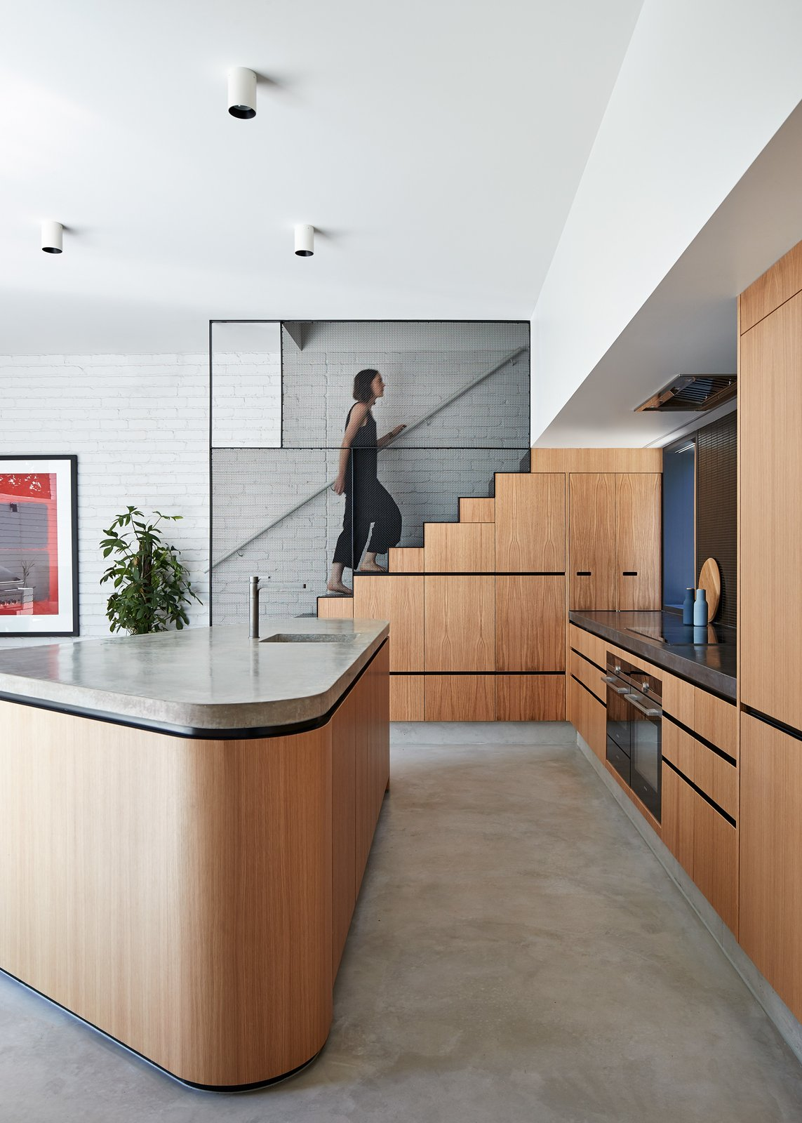 Kitchen, Concrete, Cooktops, Concrete, Refrigerator, Wood, Range Hood, Wall Oven, Ceiling, Concrete, and Undermount A steel mesh balustrade lines the stairway, which leads to the rooftop deck.  Kitchen Cooktops Undermount Concrete Photos from An Australian Home's Brick Addition Creates a Private Backyard Haven