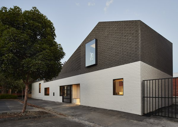 """Stitching the existing white weatherboard cottage into its more robust industrial surrounds, the new addition uses brick work painted white at the first level to connect to the white weatherboard and then black at the top level to engage with the local industrial precinct,"" say the architects."