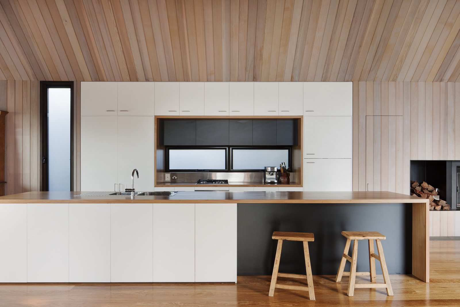 Kitchen, Medium Hardwood Floor, Refrigerator, White Cabinet, Wall Oven, Track Lighting, Wood Counter, Cooktops, and Drop In Sink A streamlined kitchen is defined by its white cabinetry against the surrounding cedar walls. The floor is composed of Ash wood.  Photo 6 of 9 in Three Connected Pavilions Form This Airy Australian Beach Retreat