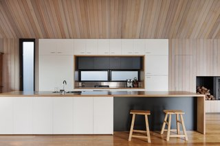 A streamlined kitchen is defined by its white cabinetry against the surrounding cedar walls. The floor is composed of Ash wood.