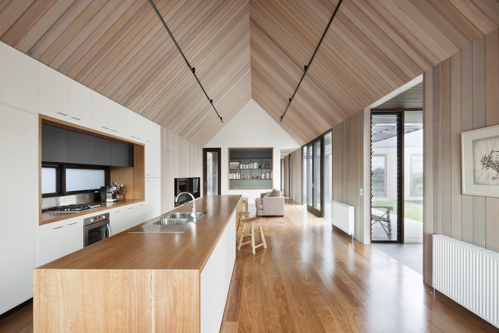 Living Room, Medium Hardwood Floor, Track Lighting, Standard Layout Fireplace, Sofa, and Stools Inside the southern pavilion of this Australian home, there is the primary open-plan living space, a study, a laundry room, and a guest bedroom and bath. A streamlined kitchen is defined by its white cabinetry against the surrounding cedar walls. Jackson Clements Burrows Architects led the project.  Photo 5 of 9 in Three Connected Pavilions Form This Airy Australian Beach Retreat
