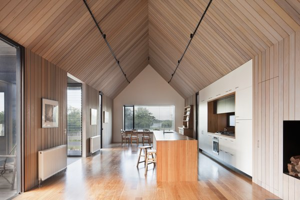 High ceilings make the narrow footprint feel more expansive. A short, glazed passage connects the polycarbonate structure to this room. That passageway also hosts the front entry.