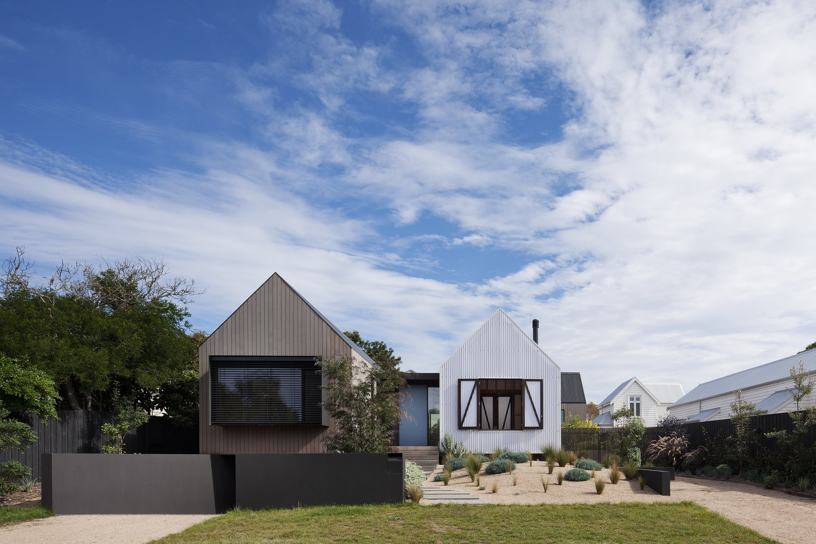 """Exterior, Metal Roof Material, Beach House Building Type, Gable RoofLine, Wood Siding Material, and House Building Type """"The gabled forms embrace the context of the surrounding post-war weatherboard houses, and the white polycarbonate directly references the white weatherboards of the dwelling to the north,"""" say the architects.  Photo 2 of 9 in Three Connected Pavilions Form This Airy Australian Beach Retreat"""