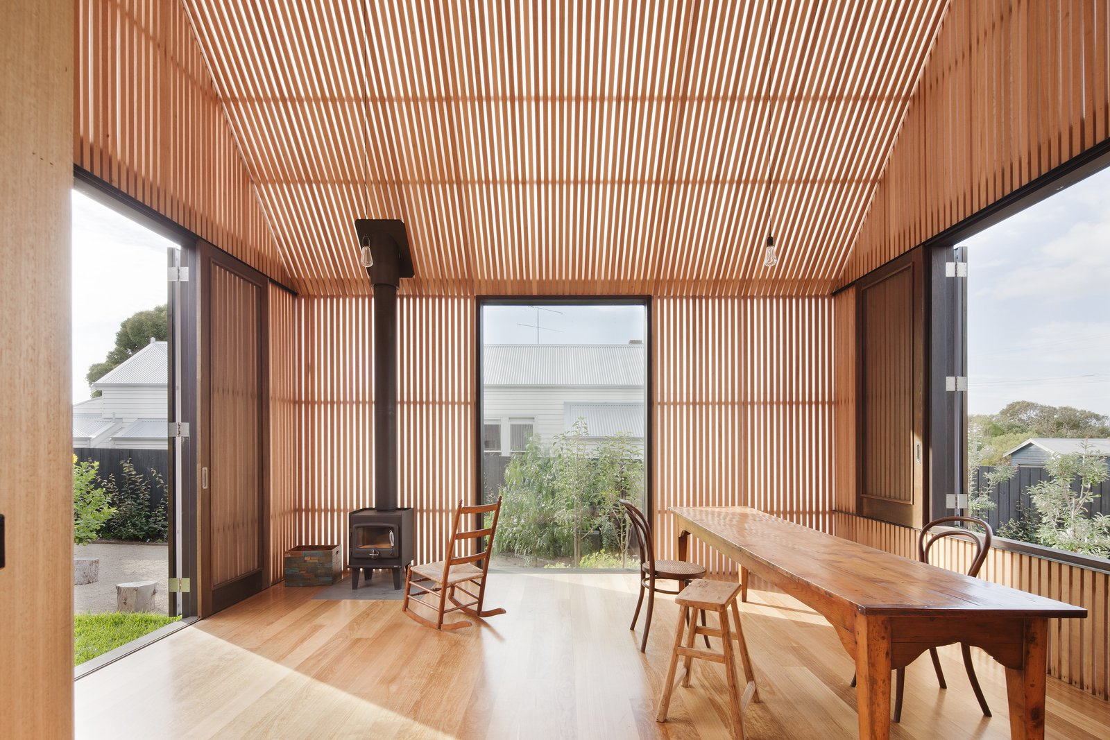 "Dining Room, Chair, Table, Wood Burning Fireplace, Medium Hardwood Floor, Pendant Lighting, and Stools The white polycarbonate structure functions as a more protected version of a porch. Timber battens provide shading and cross ventilation. ""In this case, the building is entirely clad in a triple skin, translucent polycarbonate cladding system with the inner skin entirely clad with timber battens,"" say the architects. ""This space provides cool, shaded, ventilated space in summer (doors open) and a warm, passively heated space in winter (doors closed).""  Photo 8 of 9 in Three Connected Pavilions Form This Airy Australian Beach Retreat"