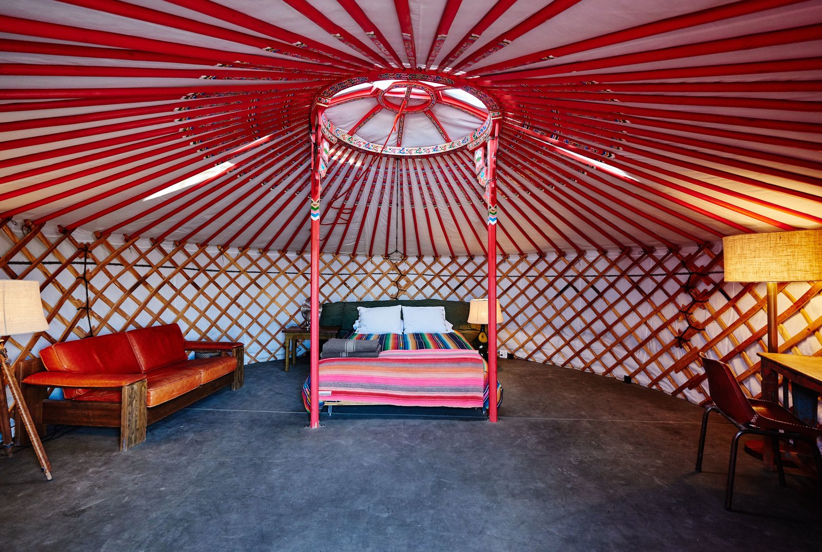 Bedroom, Night Stands, Table Lighting, Chair, Floor Lighting, Bed, and Lamps More so, El Cosmico features two yurts. Each one includes a queen-size bed, writing desk, and sofa, as well as A/C and heat.    Photo 11 of 12 in Let Your Creativity Soar at This Eclectic Hotel With Tents, Tepees, Yurts, and Trailers