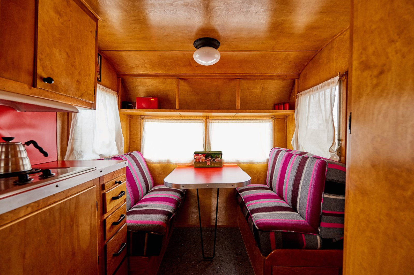Dining Room, Bench, Storage, Table, and Ceiling Lighting The bright, custom upholstery in this banquette mixes beautifully with the otherwise neutral color scheme.    Photo 7 of 12 in Let Your Creativity Soar at This Eclectic Hotel With Tents, Tepees, Yurts, and Trailers