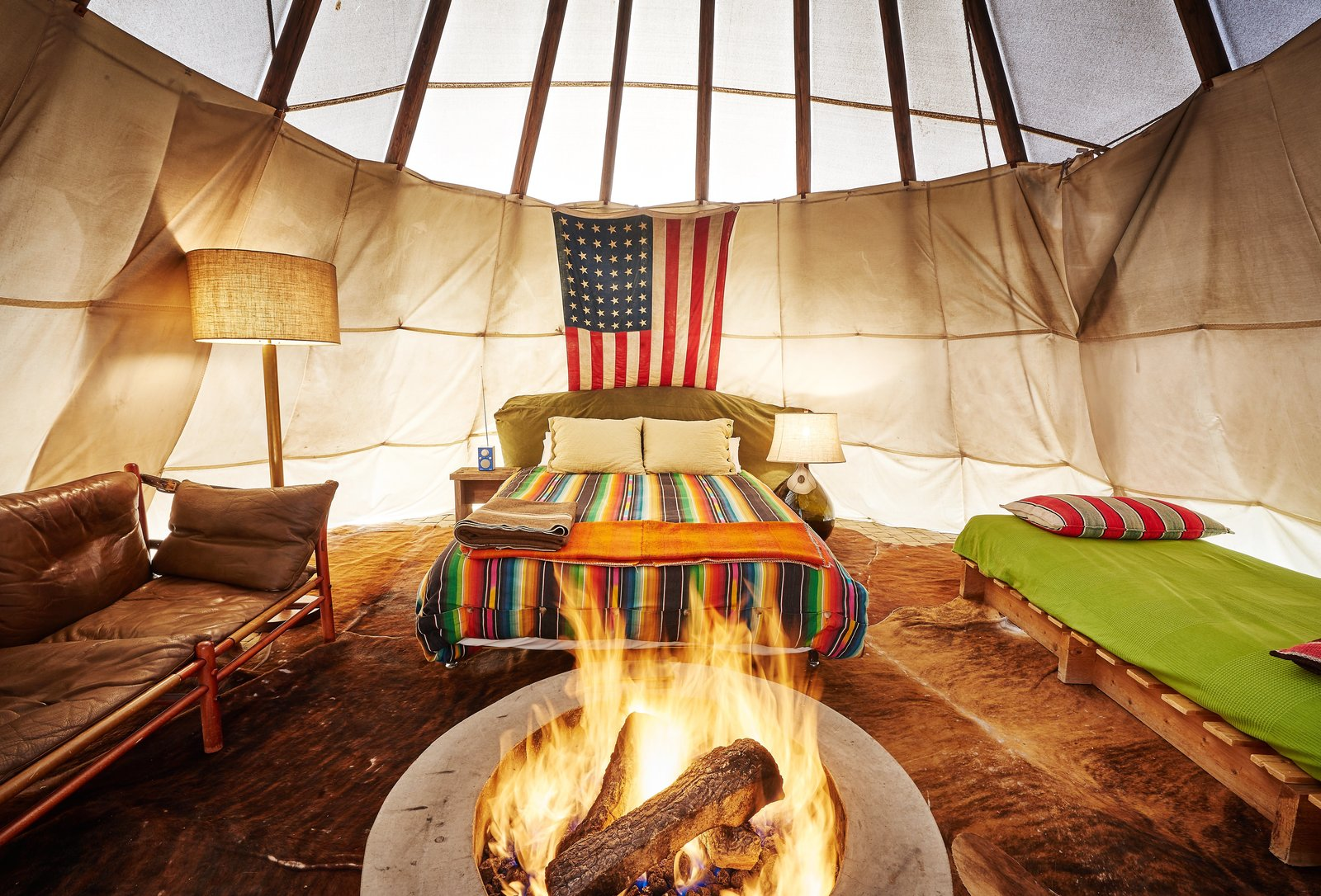 Bedroom, Bed, Lamps, Floor Lighting, Night Stands, Plywood Floor, Bench, and Table Lighting There are also five teepees on the site, each equipped with a fire pit.    Photo 10 of 12 in Let Your Creativity Soar at This Eclectic Hotel With Tents, Tepees, Yurts, and Trailers
