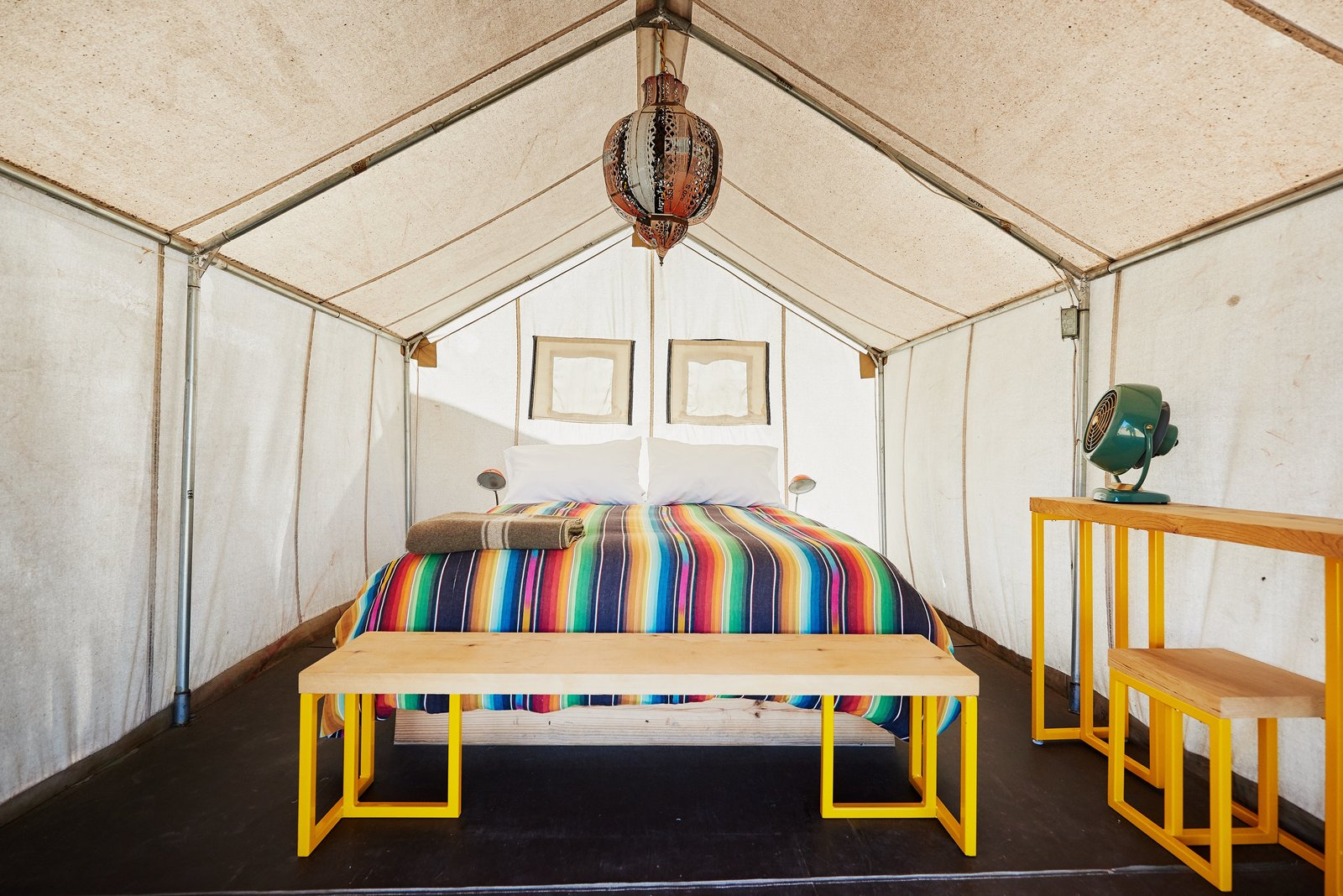 Bedroom, Table Lighting, Ceiling Lighting, Bench, and Bed Here is a look at one of the 21 safari tents. Each one is 120 square feet and comes with wooden floors and durable canvas walls/doors.    Photo 9 of 12 in Let Your Creativity Soar at This Eclectic Hotel With Tents, Tepees, Yurts, and Trailers