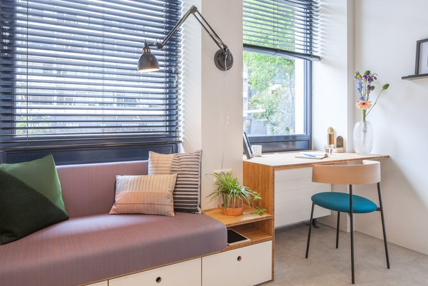 A simple desk area merges with a built-in sofa, which includes storage beneath it. The wood components in the units are bamboo, chosen for its durability and warmth.