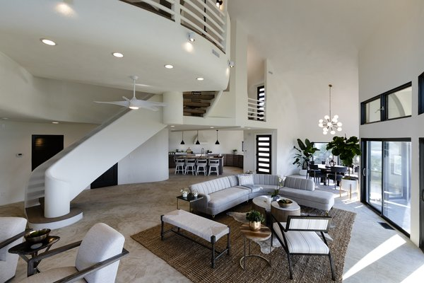 The main floor has an open living, dining, and kitchen area with unobstructed views since support beams were unnecessary for the domed structure. The floors are concrete with a decorative finish.