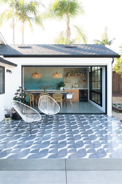 The pergola was removed, the exterior wall opened up, and a new dining room added. The 12-foot-long sliding doors, pocket doors manufactured by Western Window Systems, recede all the way into the wall for total indoor/outdoor flow. The new patio received cement tile—the Arc pattern from Clé Tile—its black and white palette coordinating with the new white paint and black window frames of the exterior.