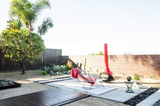The new patio connects to a fire pit lounge area via the wood walkway. Naber worked with McCullough Landscape to fashion the cement and rock patio. Decomposed granite replaced the grass, and Naber planted succulents from her wedding alongside cacti and native plants for a more drought-tolerant landscape.