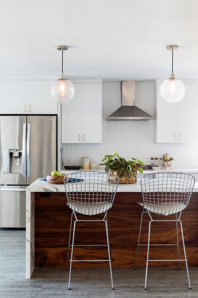 Naber revamped the kitchen with flat-front white cabinets, durable solid surface Cosentino counters by Dekton, and West Elm pendents for a light and airy destination.