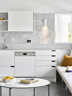 In this Australian kitchen, the open-backed portions of the upper cabinets reveal the marble tile backsplash. The marble backsplash is comprised of two parts: a low marble piece made of the same marble slab as the countertop, and then a square marble tile found elsewhere in the kitchen.