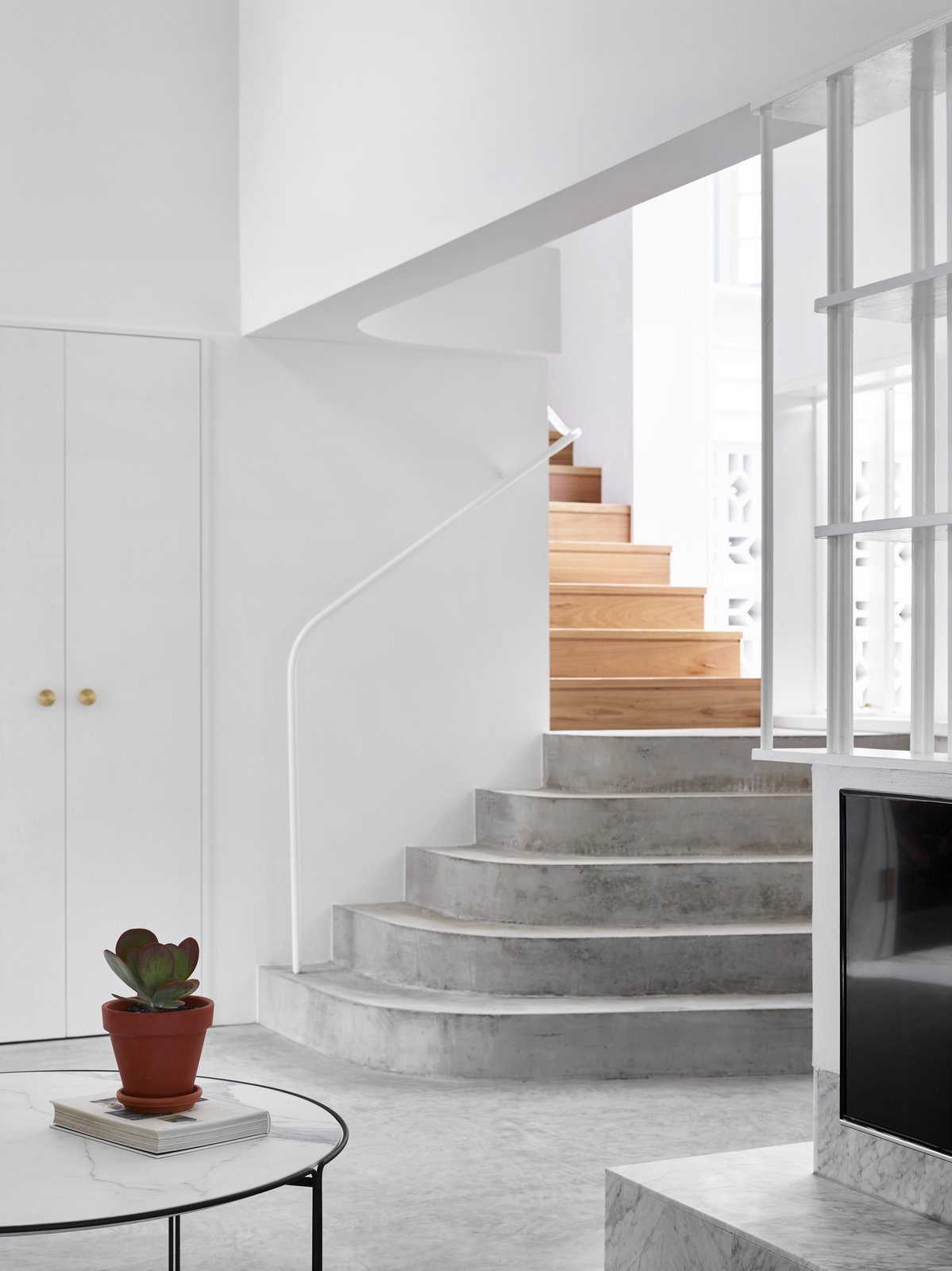 Staircase, Concrete Tread, Metal Railing, and Wood Tread Concrete and timber meet again on the stairs that lead to the upper level.  Photos from A Small Australian Cottage Becomes an Airy Gathering Hub