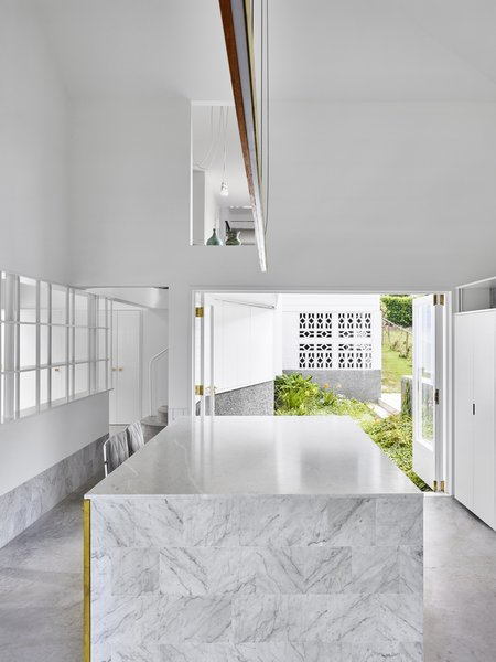 A courtyard on the other side of the kitchen makes the room feel as though it is surrounded by the outdoors. Double-height ceilings allow for a cut-out into the upper level, connecting upstairs and down.