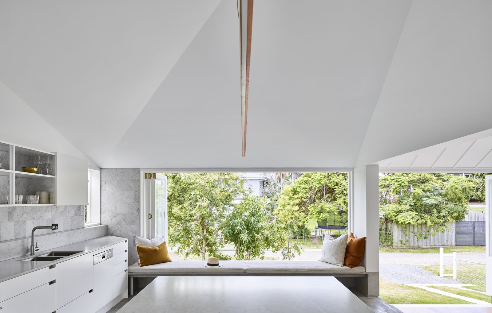 Kitchen, Marble Counter, White Cabinet, Concrete Floor, Dishwasher, Undermount Sink, Marble Backsplashe, and Pendant Lighting The kitchen window-seat overlooks the backyard garden.    Photo 5 of 12 in A Small Australian Cottage Becomes an Airy Gathering Hub