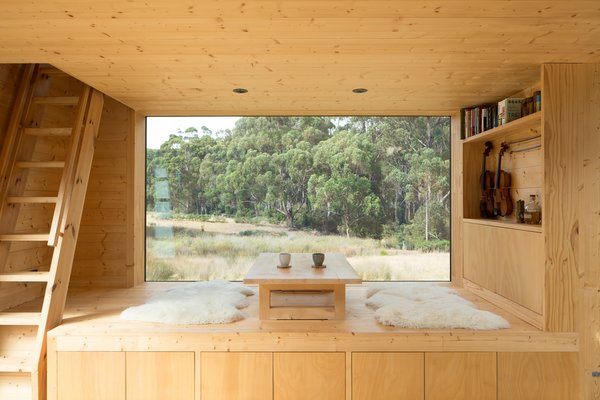 """The views to the north are unsettling, with tall, dense forest always in dark shadow,"" notes the architects. For that reason, they positioned the cabin so this serene seating area would take advantage of the southern view, which is more expansive."