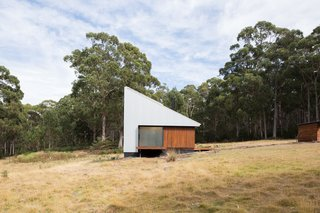 "The 301-square-foot cabin is situated on 99 acres on Bruny Island, an island off the coast of Tasmania. For the exterior, the architects have chosen materials that ""comply with the Bushfire Attack Level of 19,"" they explain, including bushfire resistant wood and zincalume metal. The cabin collects its own rainwater—storage tanks are underground for an uncluttered look—and the roof sports solar panels."