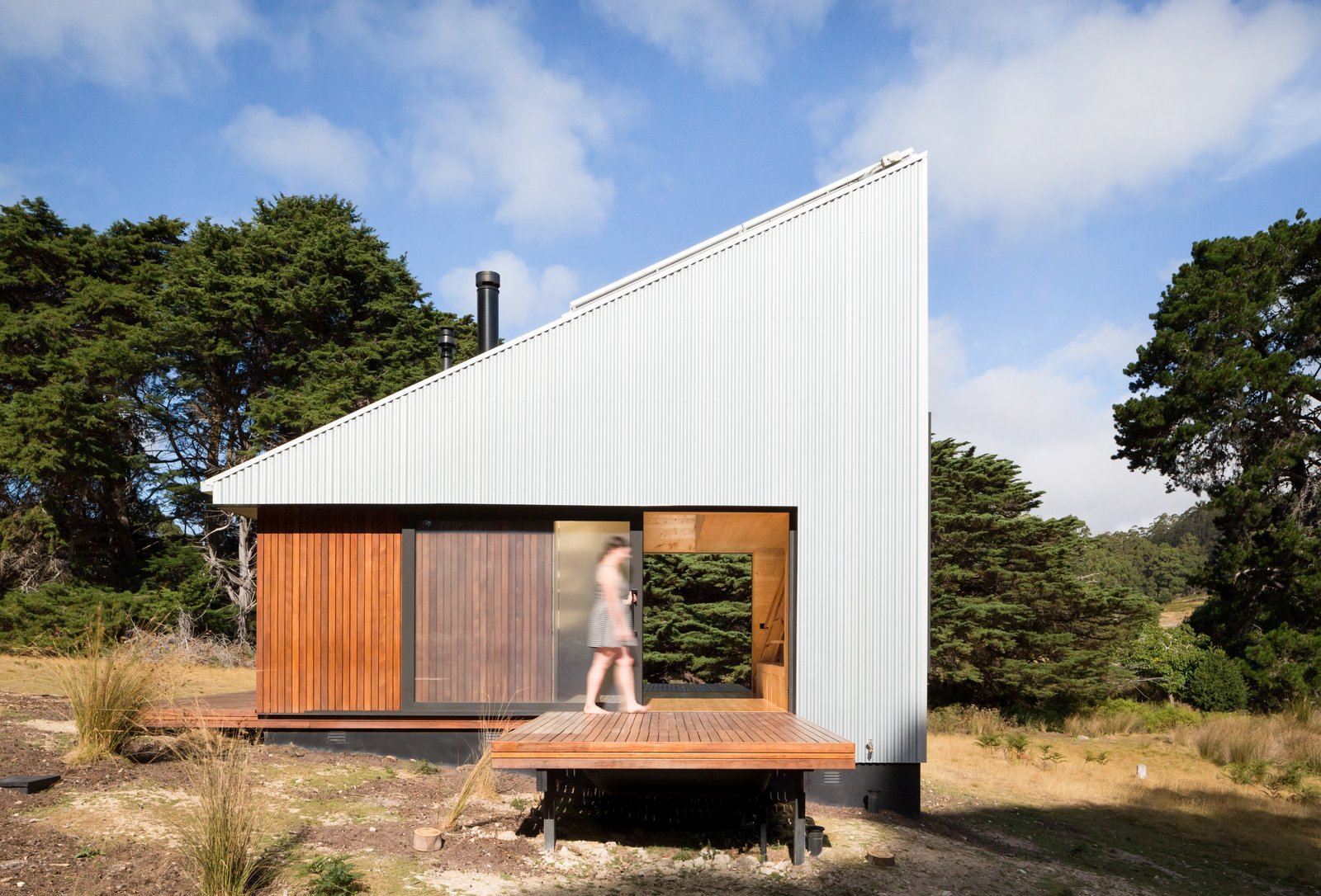 """Exterior, Wood Siding Material, Tiny Home Building Type, Cabin Building Type, Metal Siding Material, Shed RoofLine, and Metal Roof Material """"With both sliding doors open, the two decks connect seamlessly through the building, dramatically changing the sense of scale, space, and connection to the site.""""  Photos from A Secluded, Off-Grid Cabin Echoes Stunning Minimalist Design"""