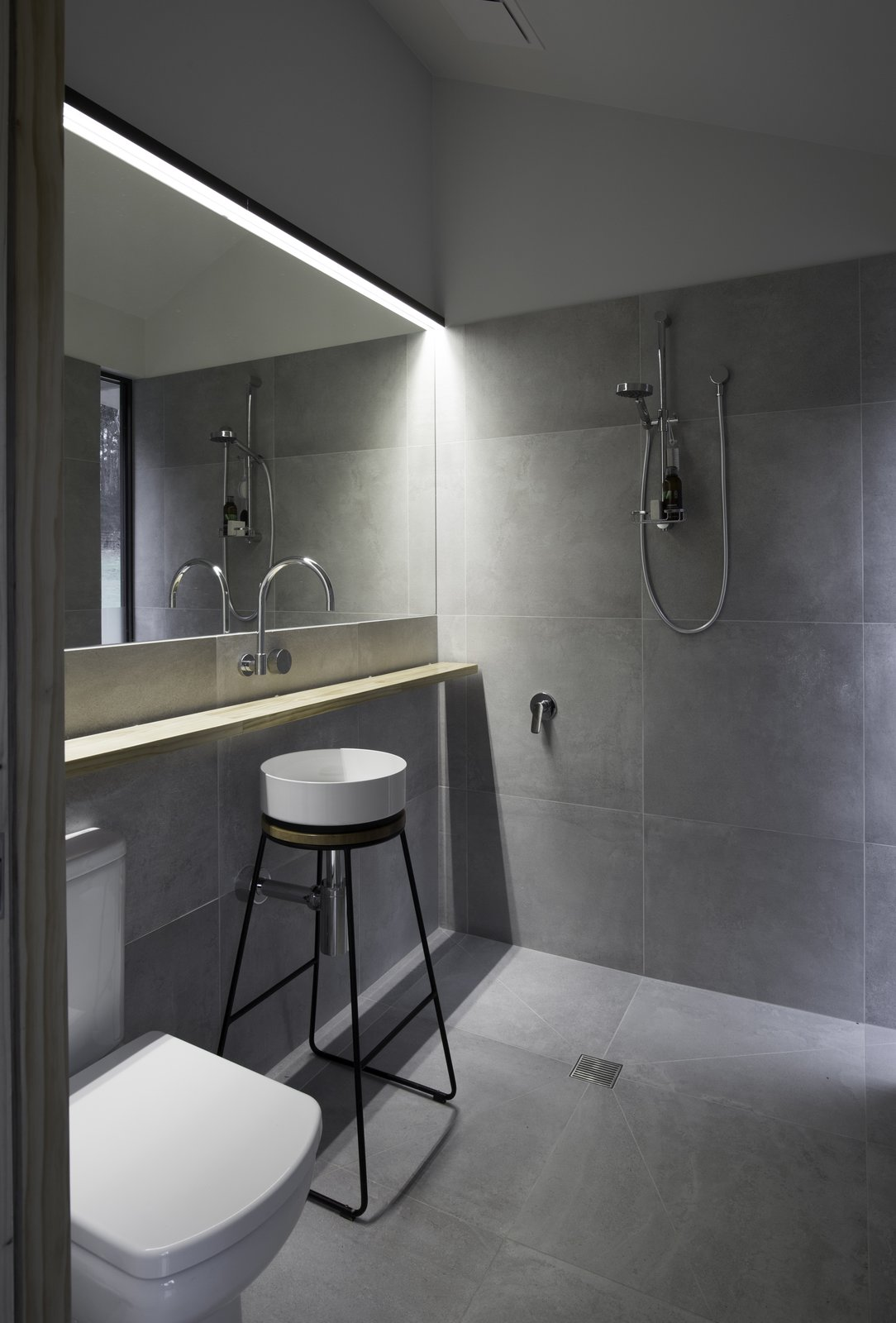 "Bath, Open, Pedestal, One Piece, Accent, and Vessel The interior bathroom can do double-duty as a mudroom, thanks to a secret door that enables exterior access. Additionally, that door delivers an ""almost"" outdoor showering experience, and has been designed so guests can use the restroom without disturbing others sleeping inside.  Best Bath Accent Open Photos from A Secluded, Off-Grid Cabin Echoes Stunning Minimalist Design"
