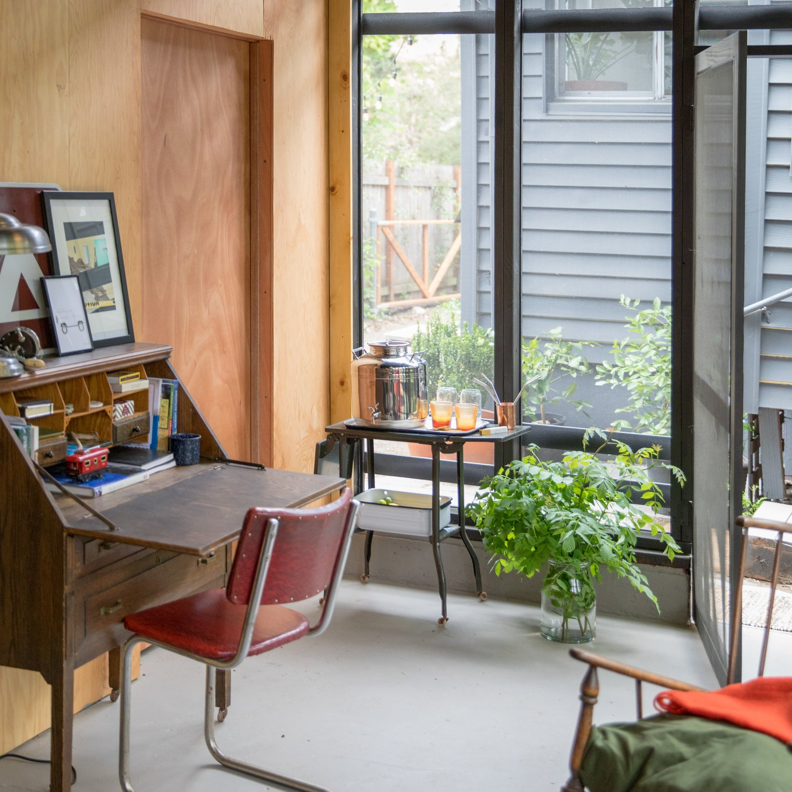 Garage, Garage Conversion, and Detached Garage The new dividing wall was sheathed in sanded pine plywood and includes a door for easy access to the other side of the garage.  Best Garage Photos from Budget Breakdown: A Weekend DIY Turns a Neglected Garage Into a Backyard Hangout For $13K