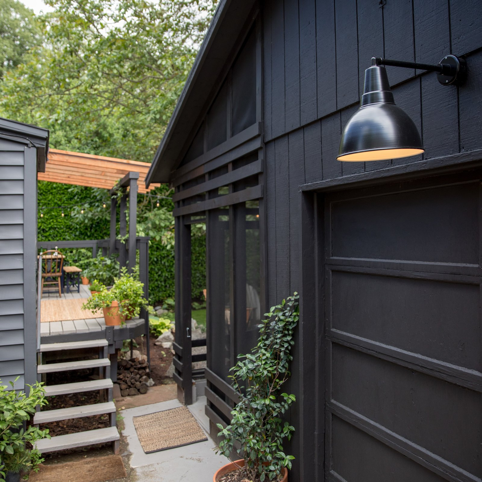 Exterior, House, Wood, and Shed A view of the new screened porch from the driveway. The light is the Factory Modern No. 6 Outdoor Sconce from Schoolhouse Electric.  Exterior Shed Wood Photos from Budget Breakdown: A Weekend DIY Turns a Neglected Garage Into a Backyard Hangout for $13K