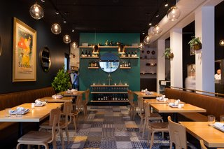 The rest of the bistro's palette, from the camel leather banquettes to the aquamarine accent wall, was chosen to compliment the beautiful floor tile.