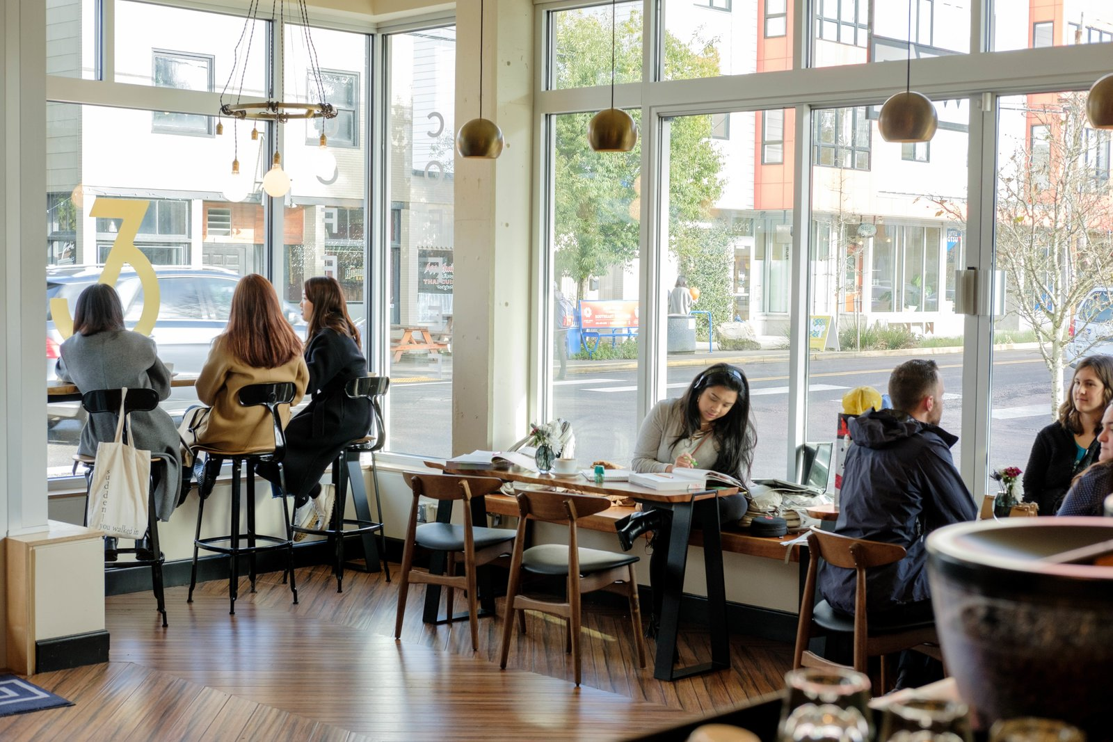 Dining Room, Table, Stools, Pendant Lighting, Medium Hardwood Floor, Chair, and Bench Lots of windows bring in lots of natural light at Dapper & Wise Coffee Roasters.  Photo 13 of 15 in 10 Best-Designed Places to Eat and Drink in Portland, Oregon