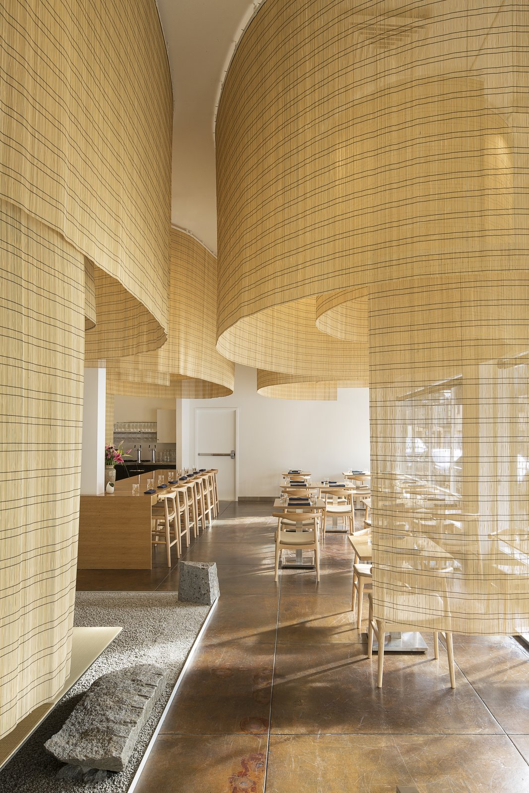 """Dining Room, Chair, Stools, Table, and Bar Kuma and his team suspended large swaths of bamboo screens from the ceiling. """"Instead of hanging it with the filaments arranged horizontally, we turned the bamboo screens ninety-degrees so that the strands were oriented vertically,"""" architect Balazs Bognar told Eater PDX. """"It's an age-old material, but used in a new way.""""  Photo 7 of 15 in 10 Best-Designed Places to Eat and Drink in Portland, Oregon"""