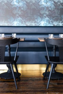 A dark blue leather banquette with a brass kick-plate syncs with the Eskayel wallpaper.