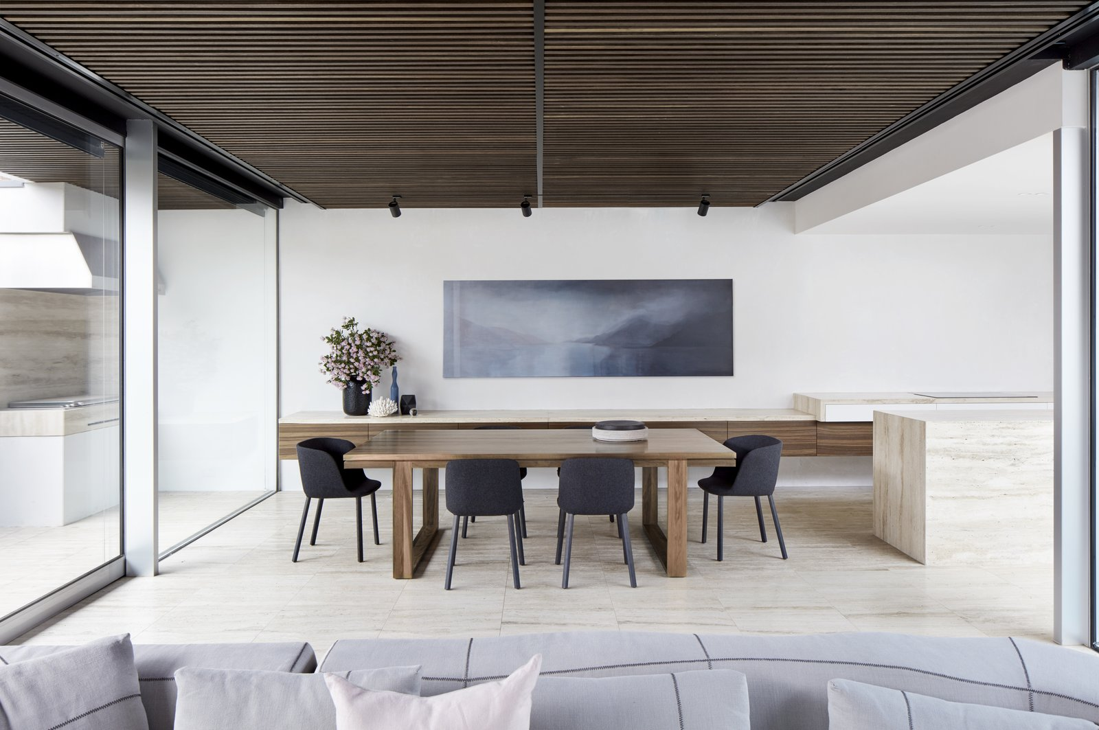 Dining Room, Travertine Floor, Track Lighting, Ceiling Lighting, Table, and Chair A built-in barbecue is just accessible on the other side of the dining room. The chairs are the Pianca 'Esse' from Meizai.    Photo 7 of 11 in Courtyards Maximize Sunlight in This Renovated Australian Abode