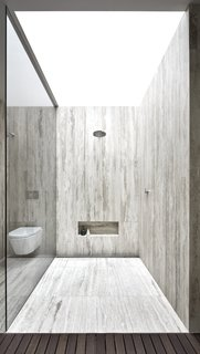 The shower is enclosed in travertine and topped with a skylight.