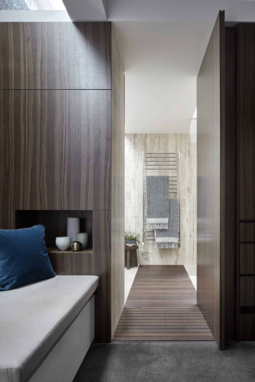 Bedroom, Bench, and Carpet Floor The view into the en-suite bathroom. The repeated use of travertine and timber creates consistency with the rest of the house.  Photo 9 of 11 in Courtyards Maximize Sunlight in This Renovated Australian Abode