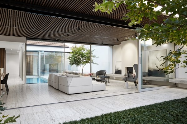 The glass addition wraps a tiled courtyard with a slim lap pool that is bordered on the other side with another landscaped courtyard.