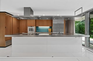 The kitchen was appropriately modernized with white lacquer and stainless steel.
