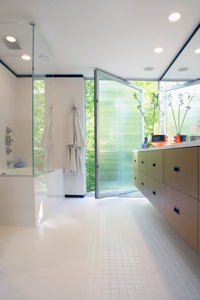 In the master bathroom, a large pivot door creates gracious indoor/outdoor flow.