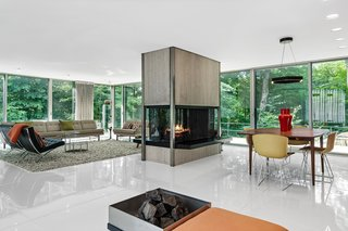 The four-sided fireplace composed of travertine and steel is a focal point for the living and dining areas.
