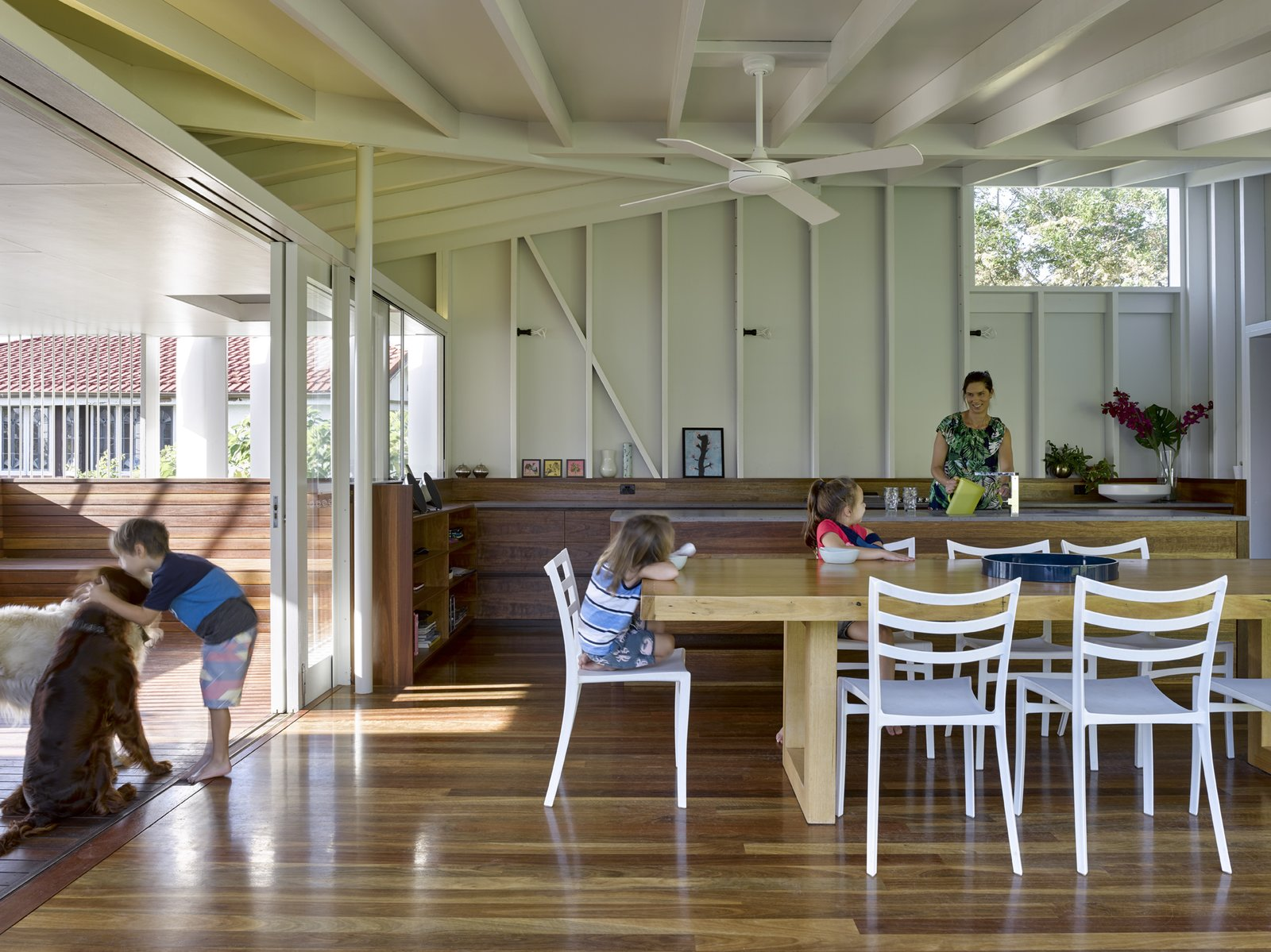 Dining Room, Table, Chair, Shelves, Medium Hardwood Floor, and Wall Lighting The pavilion relates to the original house in the exterior framework, as both use white-painted timber. Glass doors retract for full outdoor access.    Photo 5 of 8 in An Extended Garden Pavilion Enhances a 1920s Cottage