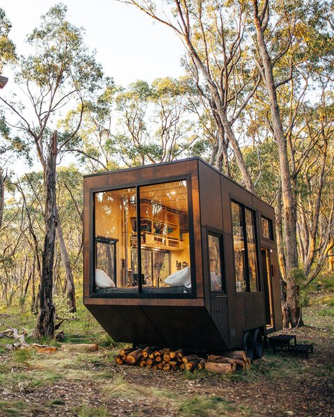 "Fed up with modern-day society's obsessive pursuit of things rather than lived experiences, Michael Lamprell, the designer of this cabin in Adelaide, Australia, set out to create an antidote to what he quips is a ""craziness we've brought upon ourselves."" In 160 square feet, CABN Jude  includes space for a king-size bed, toilet, shower, heater, two-burner kitchen stove, full-size sink, and fridge. The interior is clad with light-colored wood, which helps to enhance the sense of space. Large windows bring plenty of natural light, while the clever design means everything the resident needs is within easy reach."