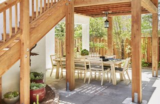 Outdoor, Shrubs, Wood Fences, Wall, Wood Patio, Porch, Deck, Large Patio, Porch, Deck, Vertical Fences, Wall, Trees, Hanging Lighting, and Back Yard The lower level area is now the perfect protected spot for al fresco dinner parties.