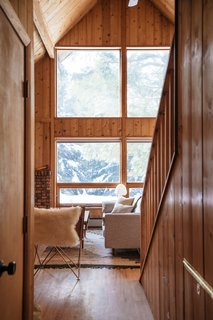 A big draw when Jenny and Allie bought the cabin were the huge windows in the main living area. The flooring was all replaced, but the knotty pine paneling was left in place in order to maintain the home's authentic Vermont charm.