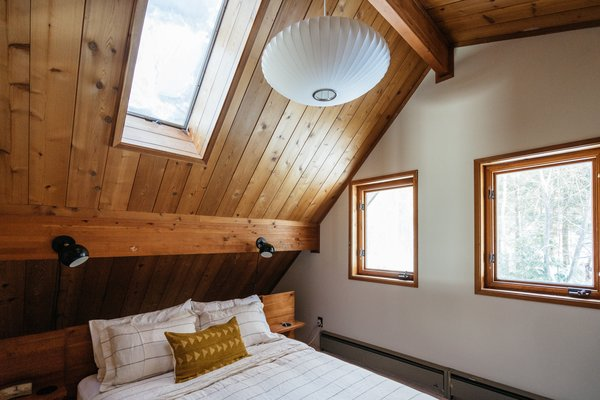 The cabin has three bedrooms. The main bedroom was brightened up with a new coat of white paint and is furnished with Schoolhouse Electric sconces, the Nelson Bubble Lamp from Design Within Reach, and linens from CB2.